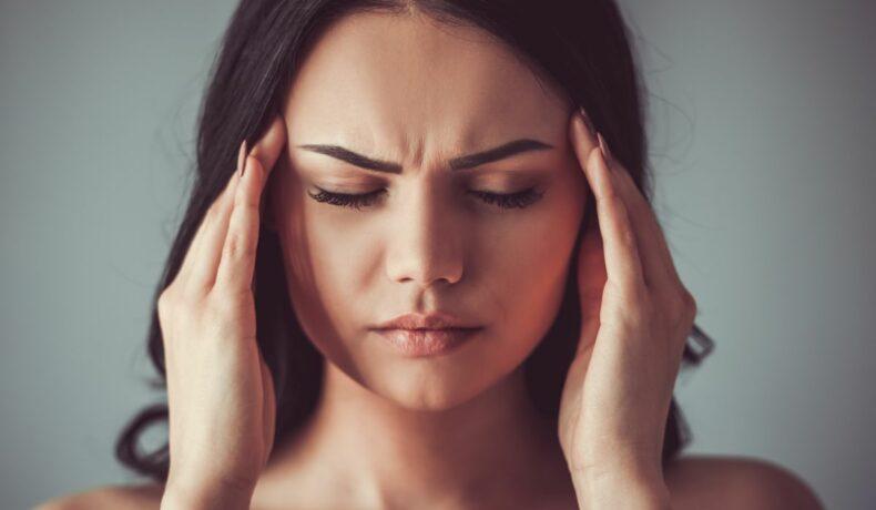 O femeie stresată, cu părul desfăcut, își atinge tâmplele