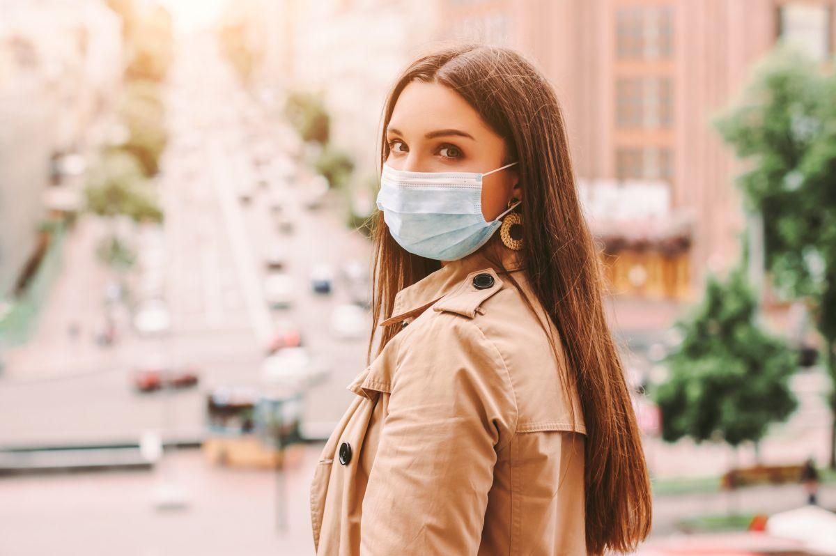 O femeie poartă mască de protecție și un trench crem, în timp ce în fundal se vede traficul intens al unui oraș.