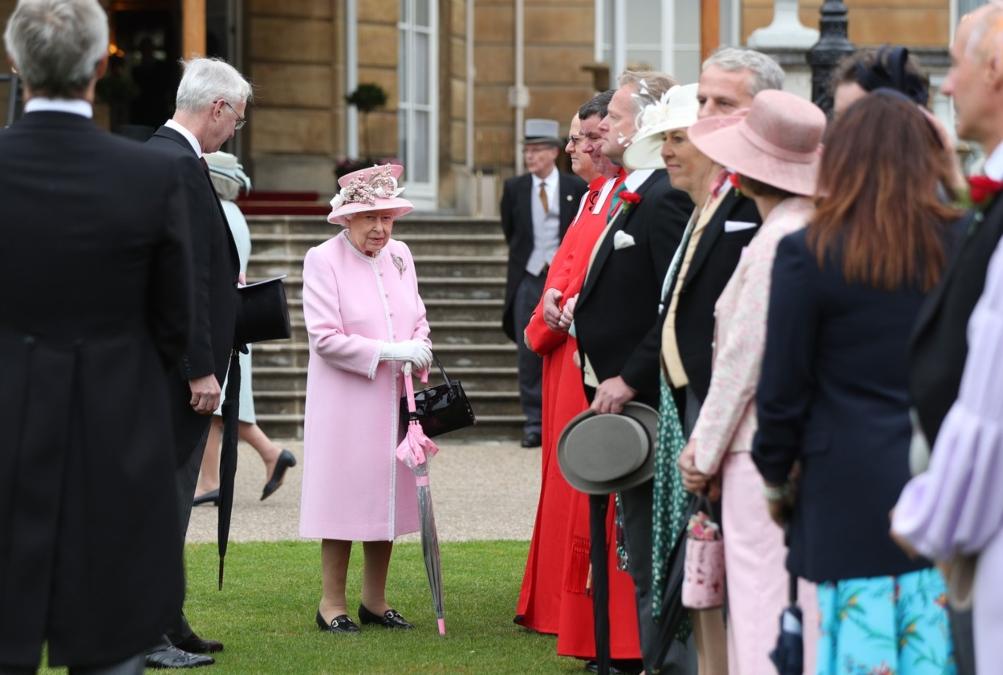 Regina în grădina Palatului Buckingham înconjurată de înalți oficiali