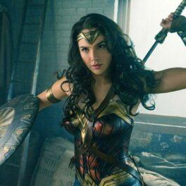 Gal Gadot costumată în Wonder Woman ține în mână o sabie și un disc de protecție