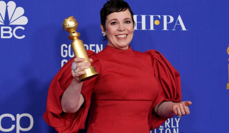 Olivia Colman îmbrăcată cu o rochie roșie pe covorul roșu ține în mână un Glob de Aur