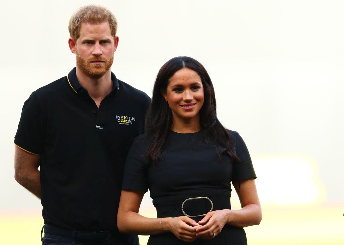 Harry și Meghan Markle, îmbrăcați în negru, zâmbesc în fața camerei de fotogtafiat.
