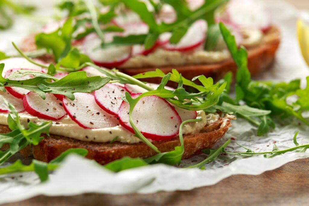 Hummus pe pâine cu salată de ridichi și rucola