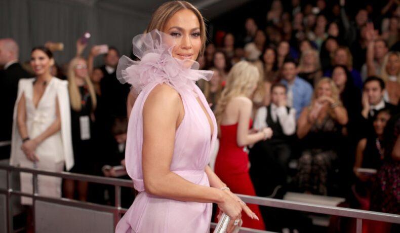 Jennifer Lopez pe covorul roșu îmbrăcată cu o rochie roz pal cu decolteu adânc și fără mâneci