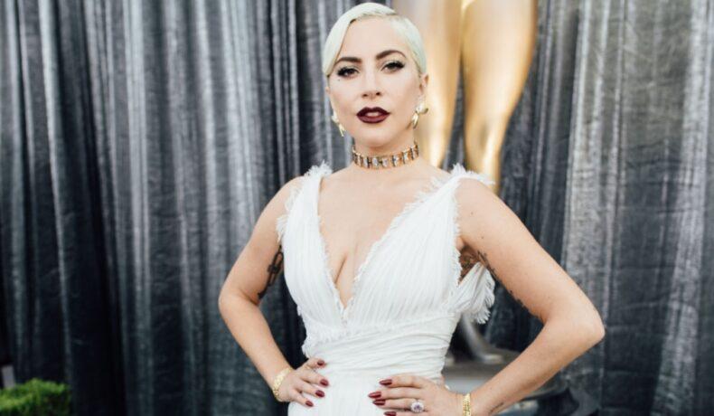 Lady Gaga la ceremonia Oscar îmbrăcată cu o rochie albă cu decolteu adânc