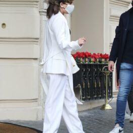 Lady Gaga îmbrăcată cu un costum alb și cizme negre cu toc înalt în fața unui hotel
