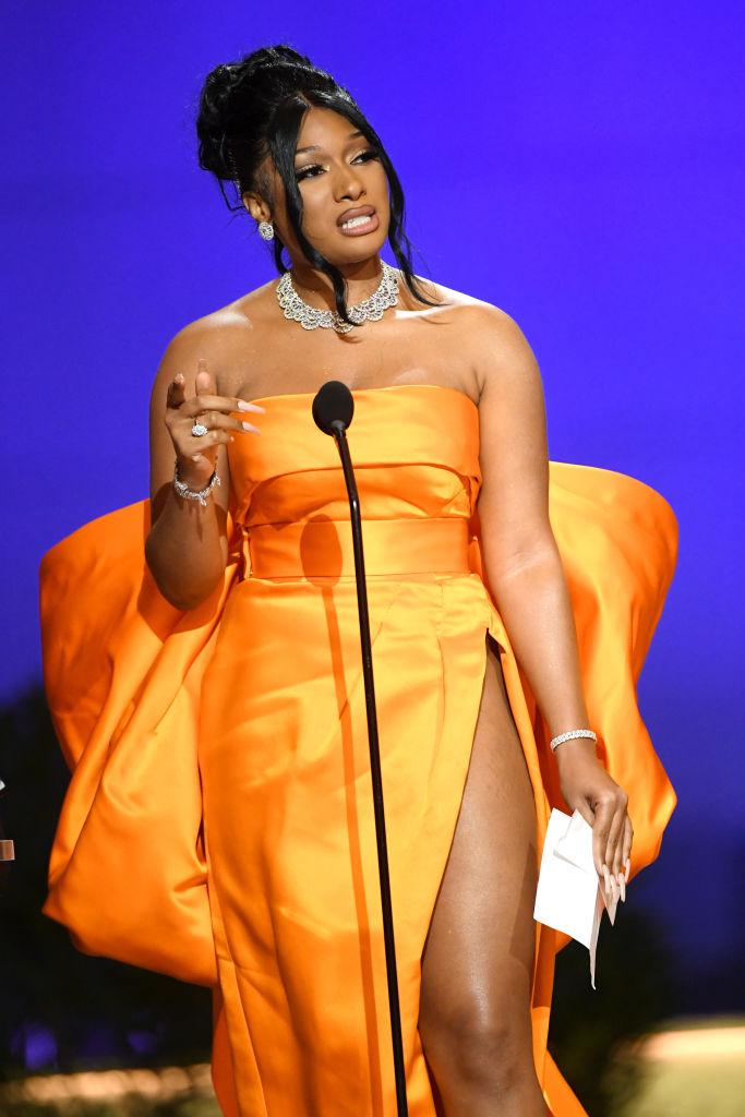 Megan Thee Stallion, pe scena Premiilor Grammy 2021, într-o rochie cu crăpătură adâncă, portocalie