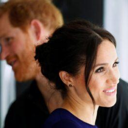 Portret cu Meghan Markle și Prințul Harry în spatele ei