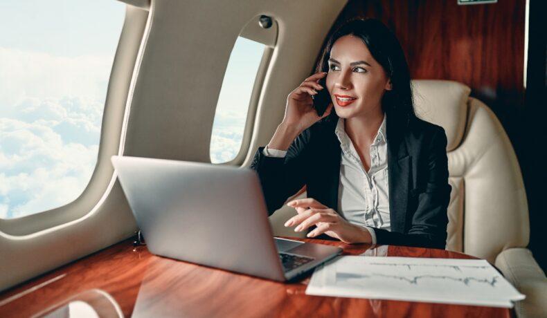 O femeie lucrează pe laptop și vorbește la telefon într-un avion privat