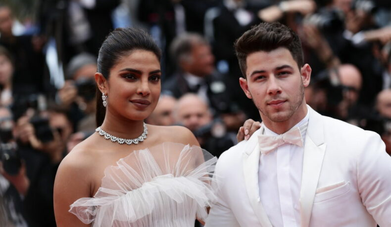 Nick Jonas îmbrăcat cu un costum elegant alb alături de Priyanka Chopra îmbrăcată cu o rochie albă pe covorul roșu