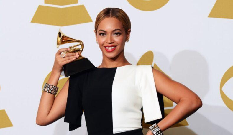 Beyonce îmbrăcată cu o rochie jumătate albă și jumătate neagră pe covorul roșu, ține un trofeu, după ce a fist nominalizată la Premiile Grammy