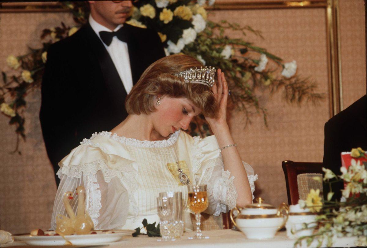 Prințesa Diana, într-o rochie albă, elegantă cu tiară pe cap, stă la masă în timpul unei vizite în Noua Zeelandă, în 1993.