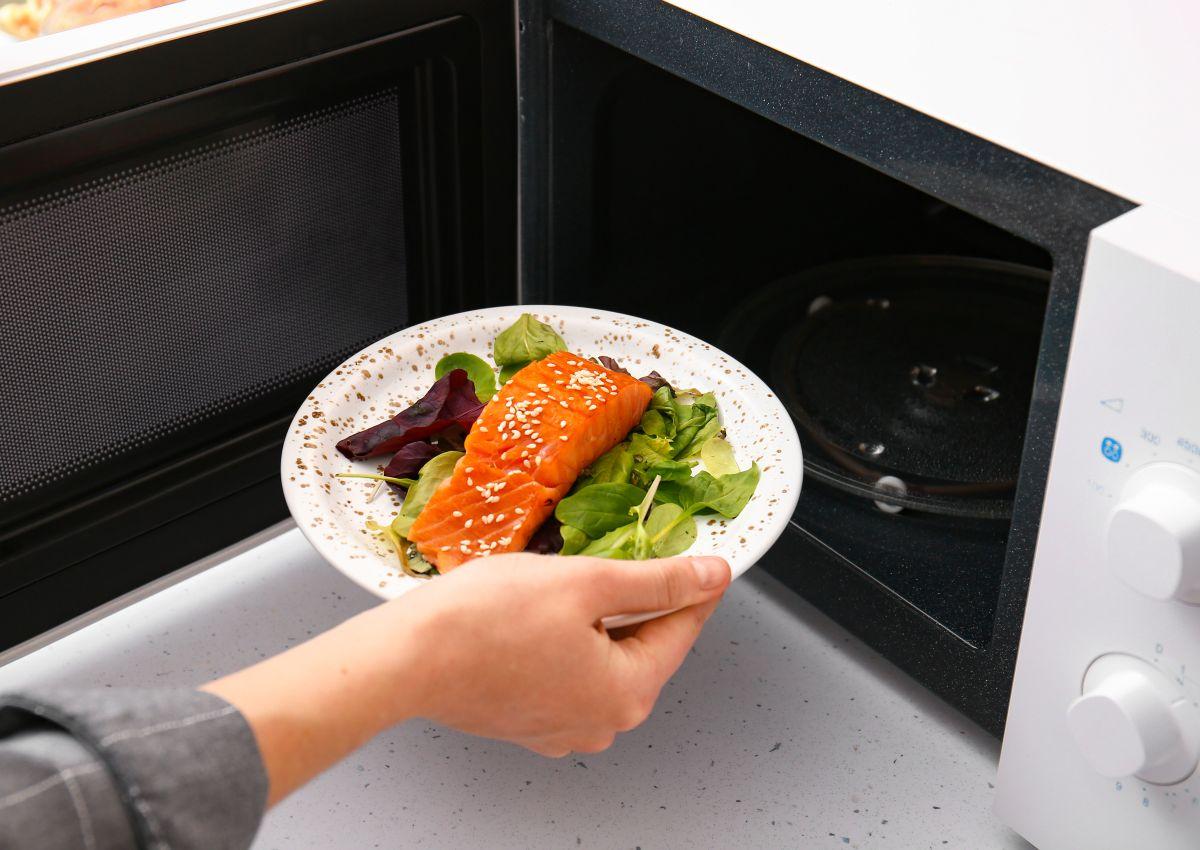 O femeie introduce în cuptorul cu microunde o farfurie cu salată și somon.