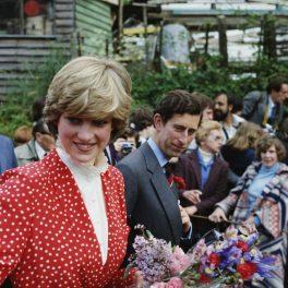 Lady Diana, alături de Prințul Charles, poartă o rochie roșie, cu buline și guler încrețit, și ține în mână un buchet de flori.