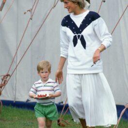 Prințesa Diana, îmbrăcată în alb, alături de Prințul Harry care ține în mâini o farfurie cu căpșuni. Fotografie realizată în anul 1987.