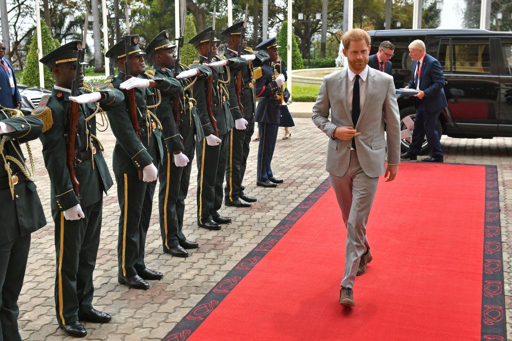 Prințul Harry îmbrăcat cu un costum gri deschis merge pe covorul roșu înconjurat de militari
