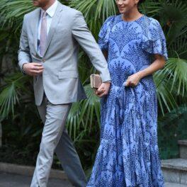 Prințul Harry îmbrăcat cu un costum gri deschis o ține de mână pe Meghan Markle îmbrăcată cu o rochie albastră lungă