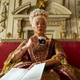 Regina Charlotte bea o ceașcă de ceai în timp ce stă pe tron în Bridgerton