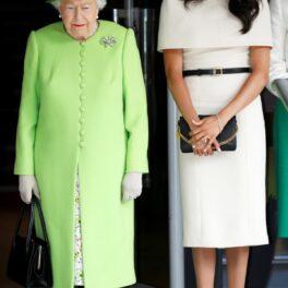 Regina Elisabeta a II-a, îmbrăcată într-un costum verde fistic, alături de Meghan Markle, care poartă o rochie de culoare albă, accesorizată cu o curea subțire neagră.