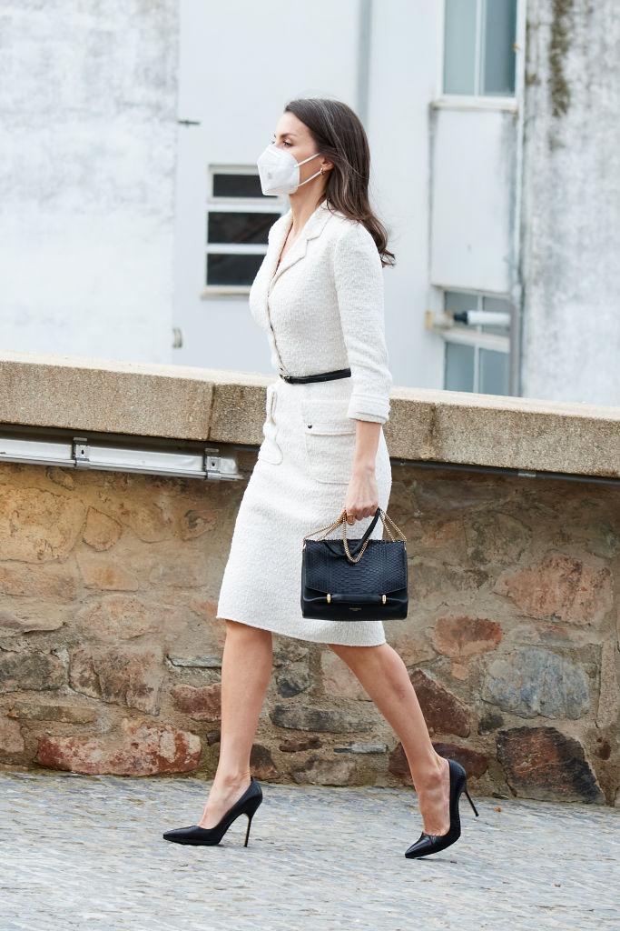 Regina Letizia, îmbrăcată într-o rochie albă, la care a accesorizat o pereche de pantofi stiletto și o poșetă neagră