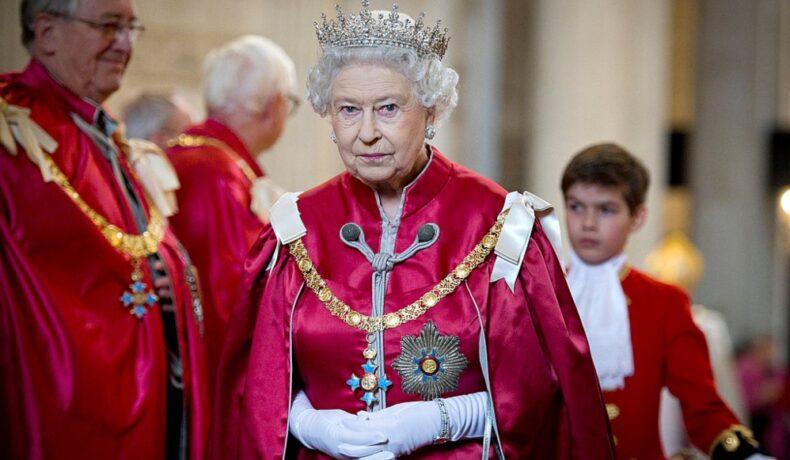 Regina îmbrăcată cu un costum roșu din satin cu capă și coroană pe cap la un eveniment