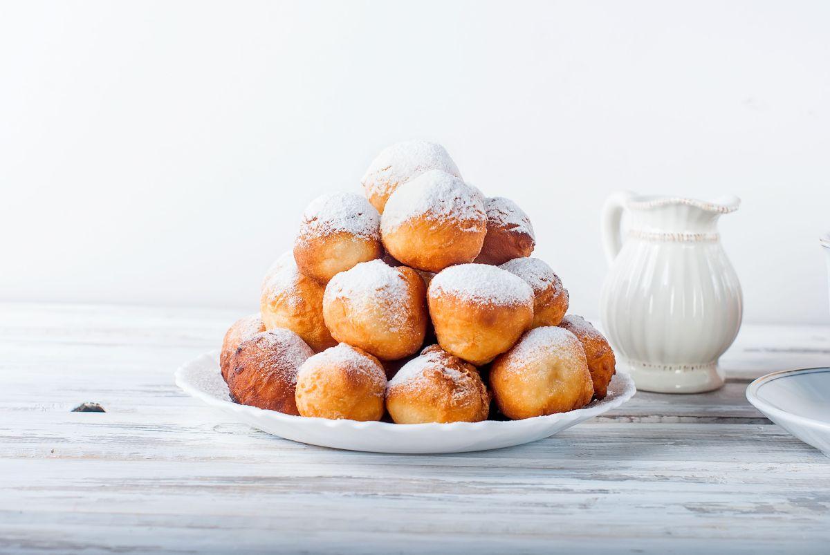 Gogoși cu iaurt, așezate pe un platou alb, pudrate cu zahar macinat fin.