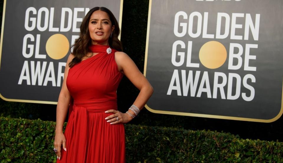 Salma Hayek îmbrăcată cu o rochie roșie lungă cu un umăr gol pe covorul roșu la Globurile de Aur