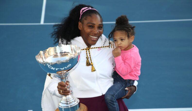 Serena Williams își ține fiica ăn brațe și trofeul în mână pe terenul de tenis
