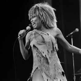 Tina Turner, fotografiată pe scenă în 1983, în timp ce ține un microfon în mână și poartă o rochie scurtă, sfâșiată.