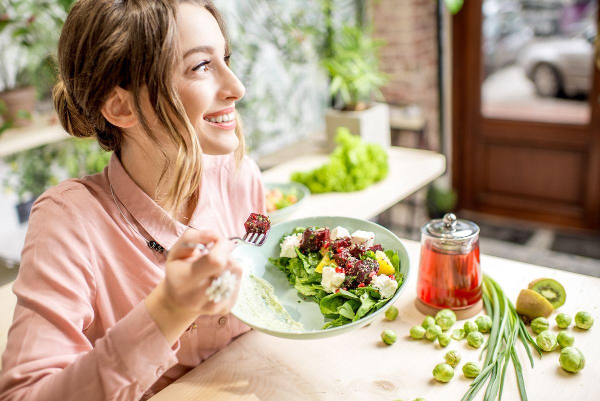 Femeie tânără, care zâmbește, în timp ce mănâncă o salată