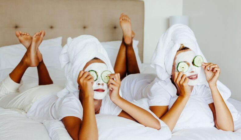 Două femei, la spa. Ambele sunt pe un pat cu lenjerie albă, cu prosoape albe pe cap, cu măști albe pe față și cu castraveți proaspeți pe ochi.