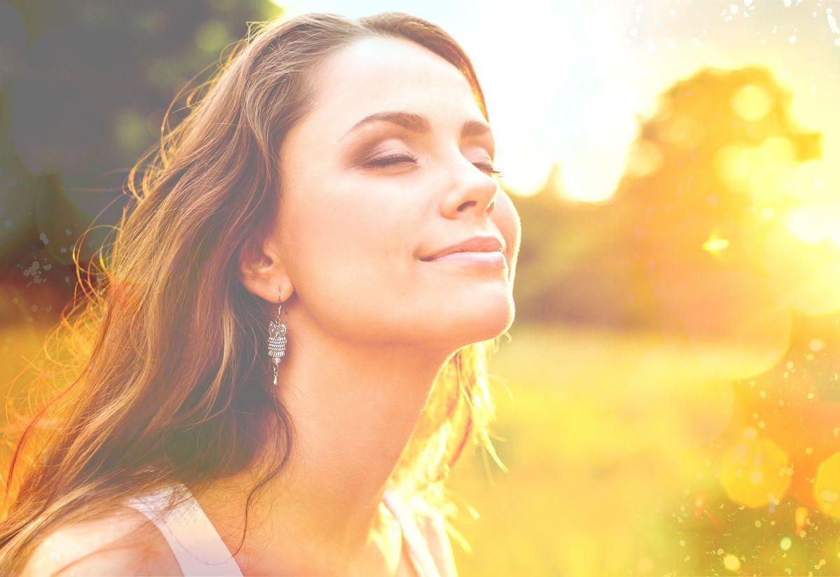 Tânără ce are ochii închiși, se bucură de lumina soarelui și de natură