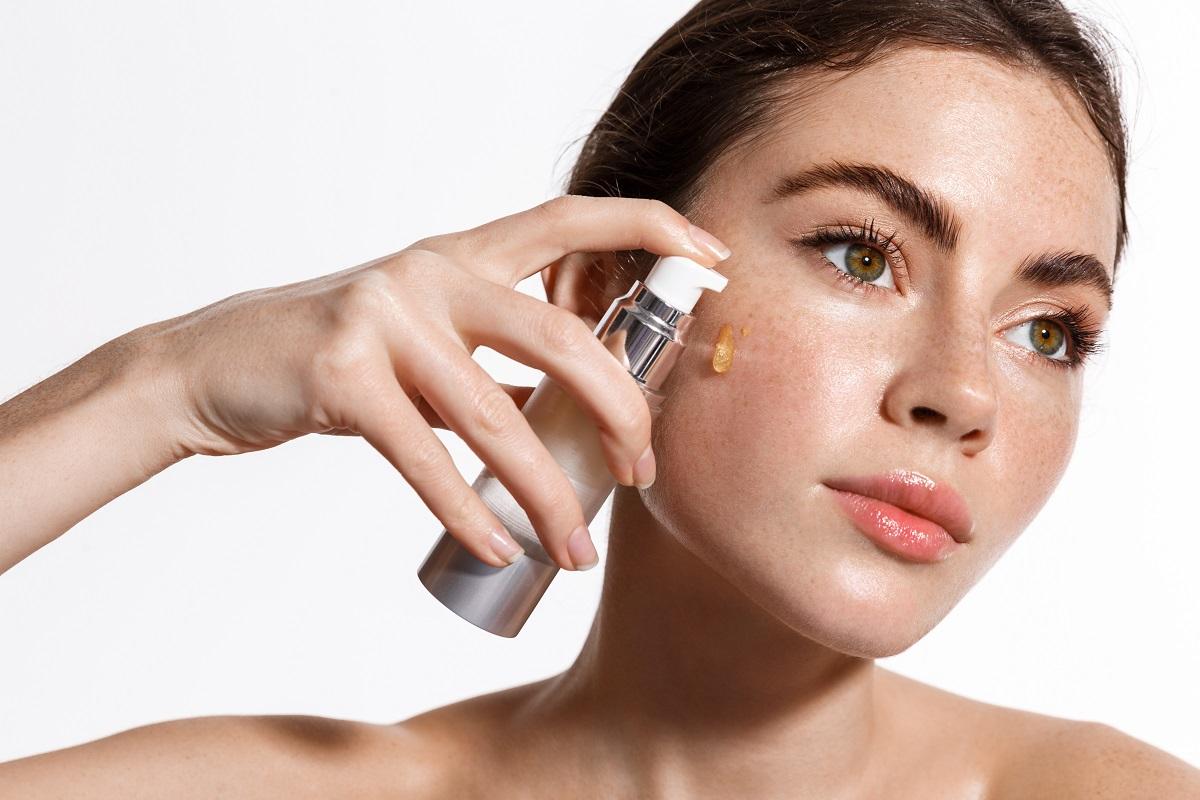 Femeie cu ochii verzi, care își aplică pe ten un produs destinat pentru estomparea porilor dilatați.