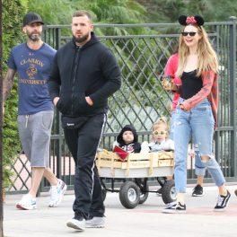 Adam Levine, într-o ținută lejeră, alături de Bhati Prinsloo, ce poartă urechi de Minnie Mouse, și cele două fete ale lor, într-o mică remorcă, cu ocazia Halloween-ului