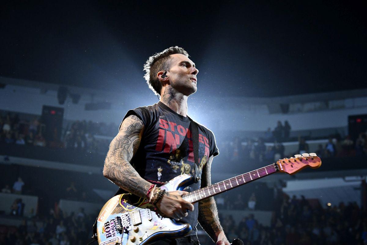 Adam Levine, solistul trupei Maroon5, cu chitara în mână, la unul dintre concertele sale
