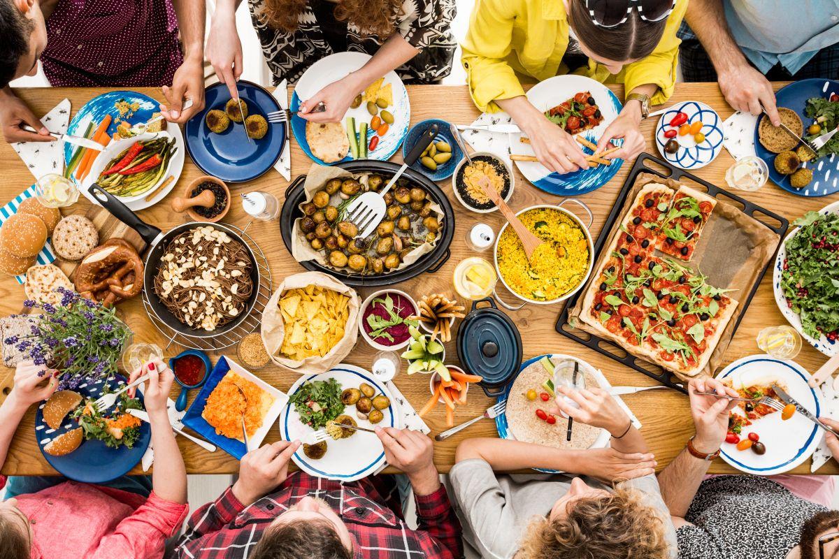 O masă de lemn, pe care stau mai multe farfurii cu mâncare, la care participă mai mulți prieteni