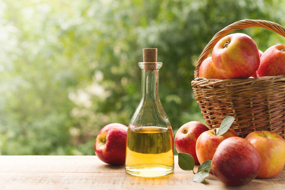 O sticlă cu dop ce conține oțet de mere, pe o masă de lemn, lângă un paner cu mere