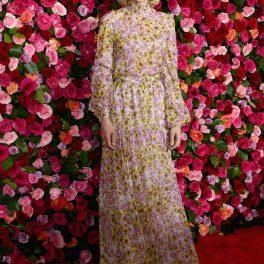 Carey Muligan, pe covorul roșu, participând la premiile Tony din 2018, îmbrăcată într-o rochie florală, pozând în fața unui panou de trandafiri.