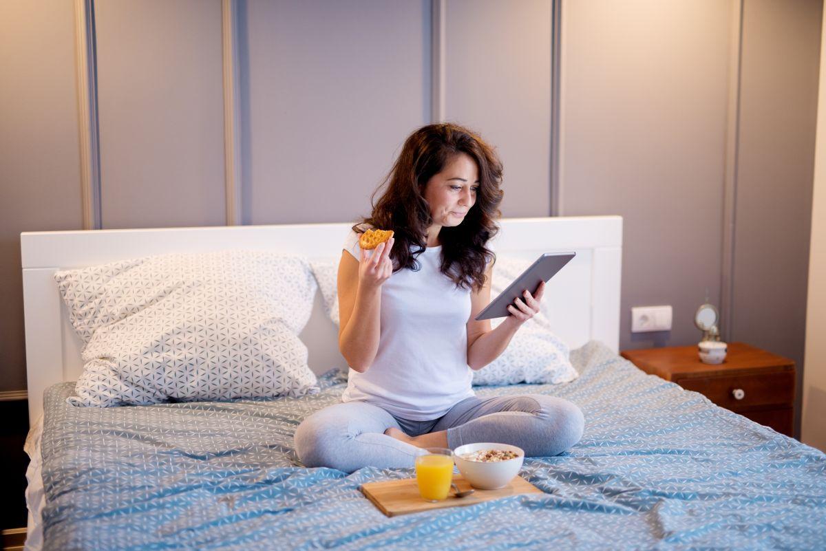 Femeie brunetă, de vârstă mijlocie, mănâncă, în poziția lotusului, pe pat
