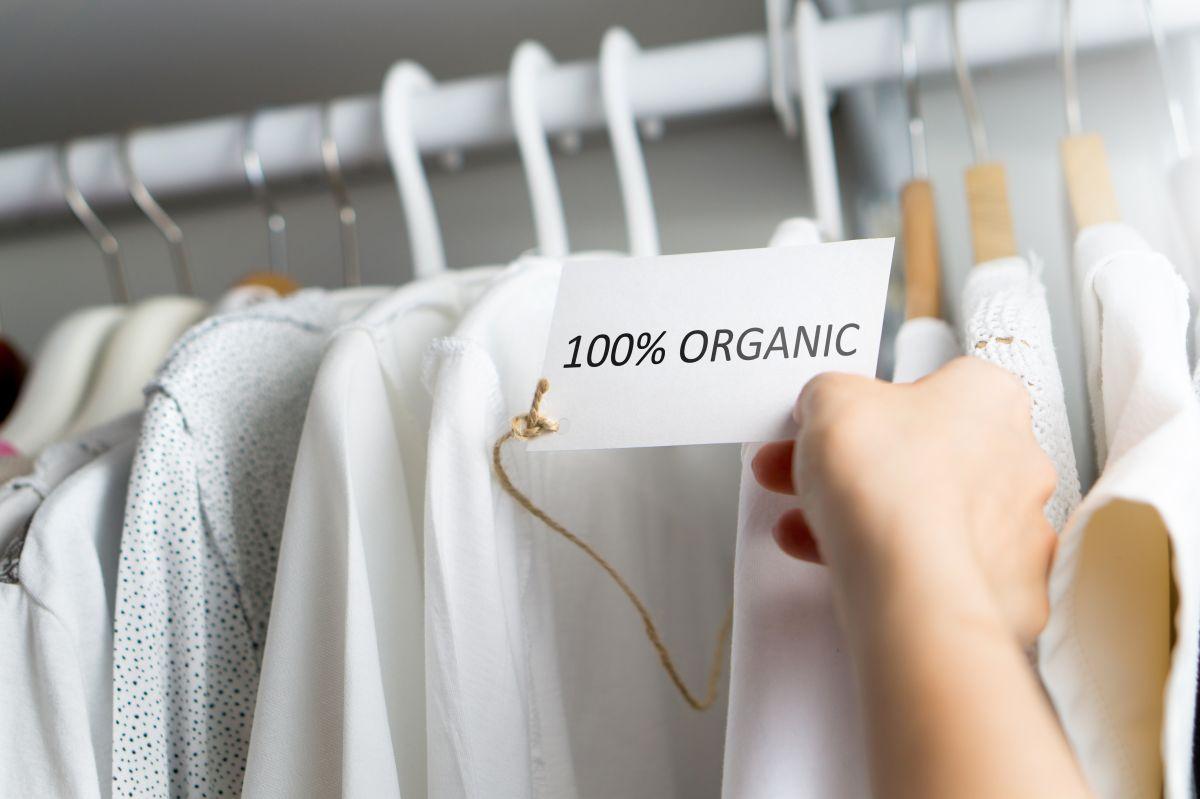 Haine albe, ce stau pe umerașe, atârnate de o bară, cu etichetă care confirmă că acestea sunt organice 100%