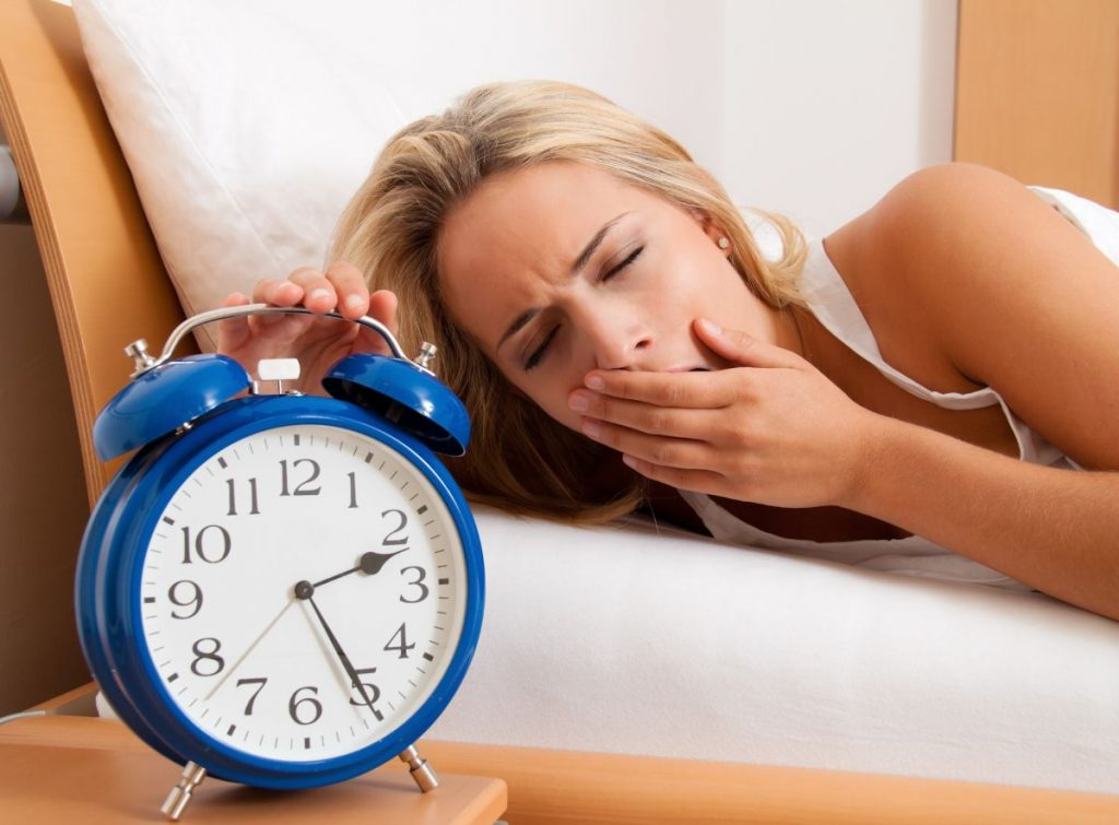 Femeie blondă, care își acoperă gura, căscând de oboseală. Aceasta este îmbrăcată într-un maiou alb și se află într-un pat din cadru de lemn.