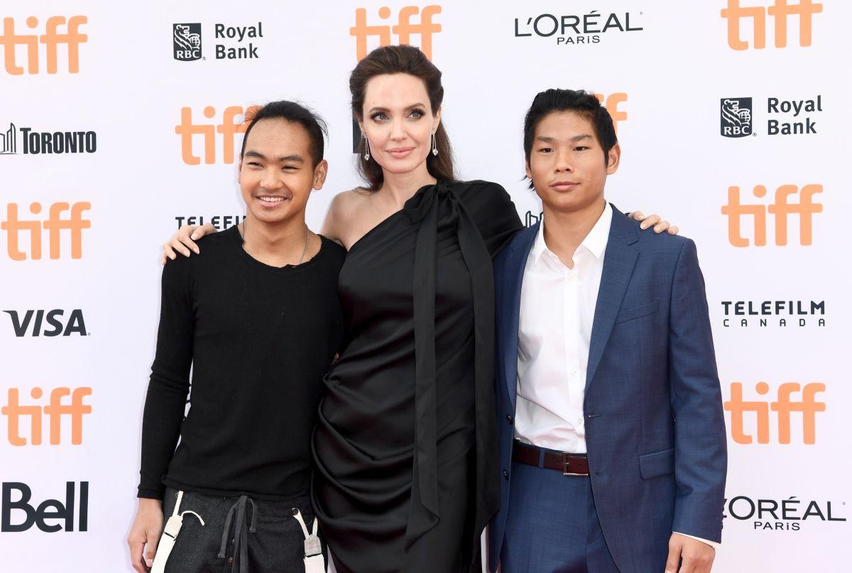 Angelina Joie, îmbrăcată într-o rochie de culoare neagră, se fotografiază alăturid e doi dintre fii săi