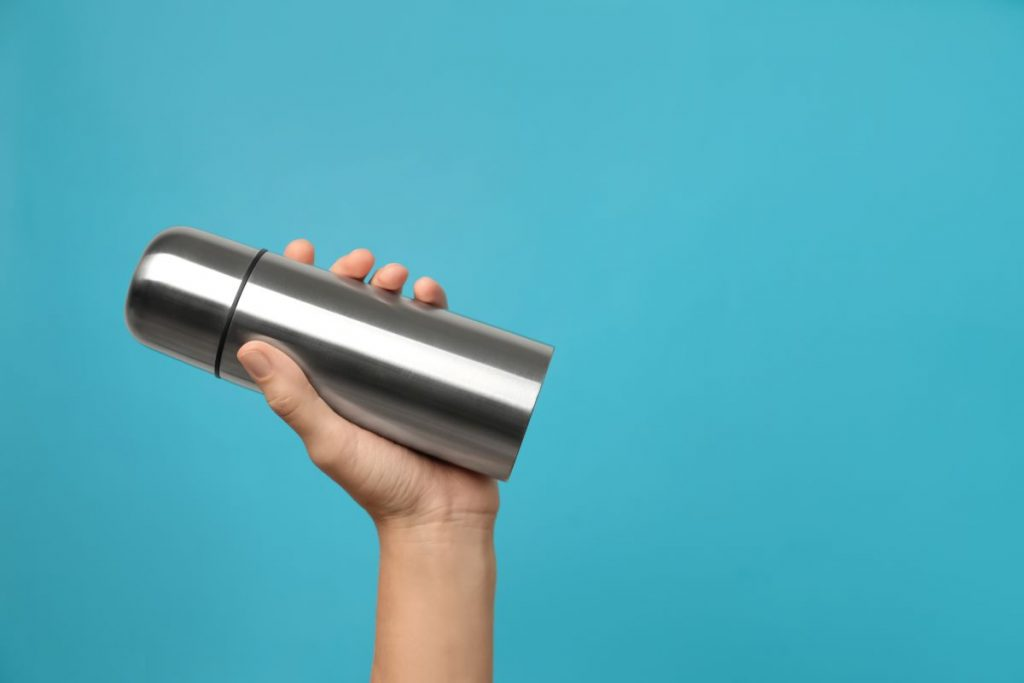 Mâna unei femei, ținând un recipient reutilizabil din aluminiu, pe un fundal azur