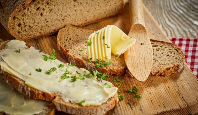 Felie de pâine, unsă cu unt, care are deasupra pătrunjel, lângă o pâine tăiată și un cuțit