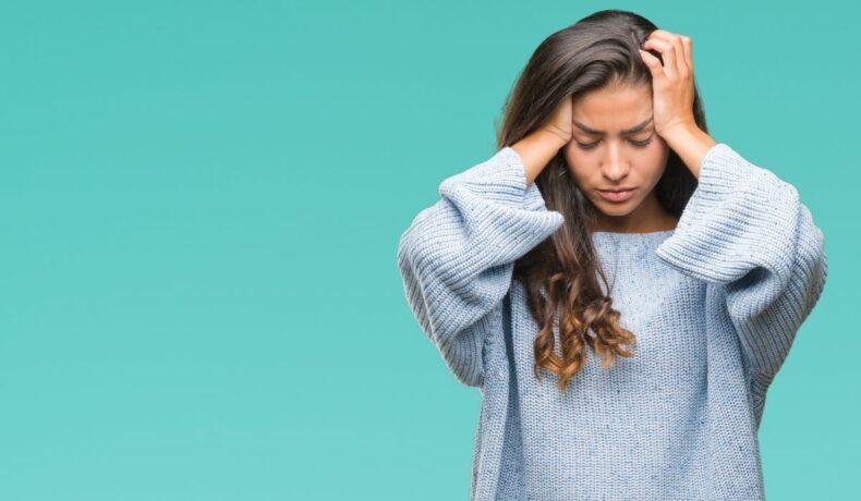 O tânără femeie, ce poartă un pulover albastru de iarnă, își ține tâmplele îmn palmă, din cauza unei dureri de cap