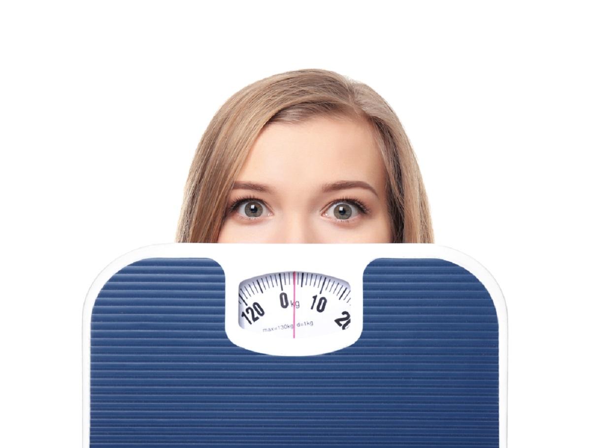 O femeie își ascunde partea inferioară a feței în spatele unui cântar de culoare albastră, pentru că își dorește să scape de kilogramele în plus într-un mod sănătos