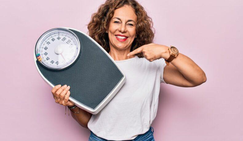 Femeie de vârstă mijlocie, zâmbește, în timp ce arată cu degetul arătător stâng, spre cântarul pe care îl ține în cealaltă mână