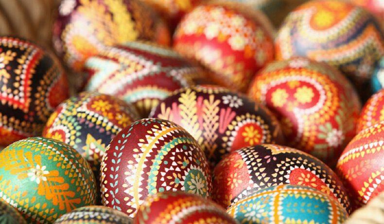 Ouă frumos încondeiate cu diferite modele și culori care ilustrează cum se sărbătorește Paștele în alte țări de pe glob