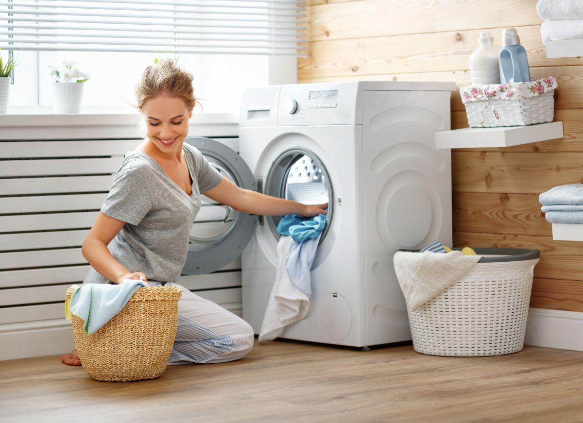 O femeie, în pantaloni albi și tricou gri, utilizează mașina de spălat