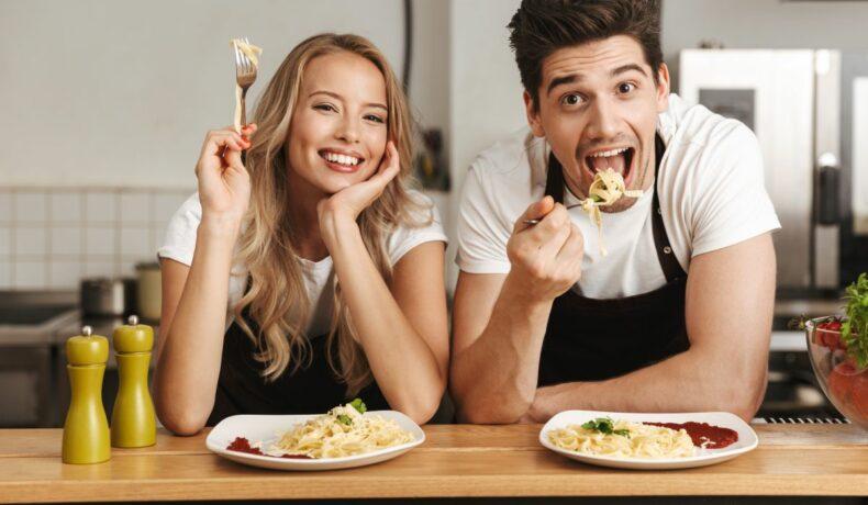 Un cuplu, care stă cu coatele pe masă, în fața a două farfurii cu paste, cu furculițele în mână, pregătindu-se de masă